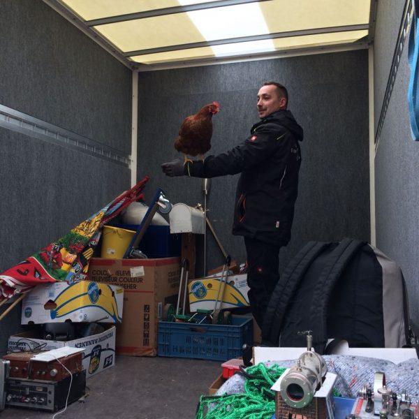 Bild von einem Huhn auf einem Arm von einem Mann