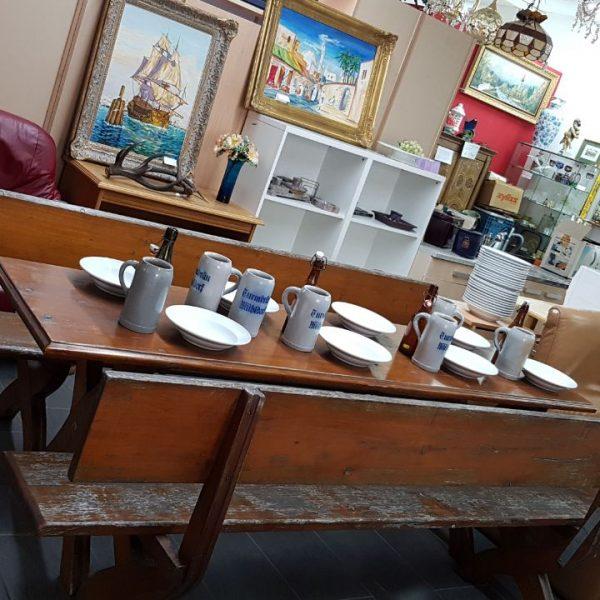 Bild von einem Gedeckten Tisch mit Gebrauchten Gemälden und Perücken im Hintergrund