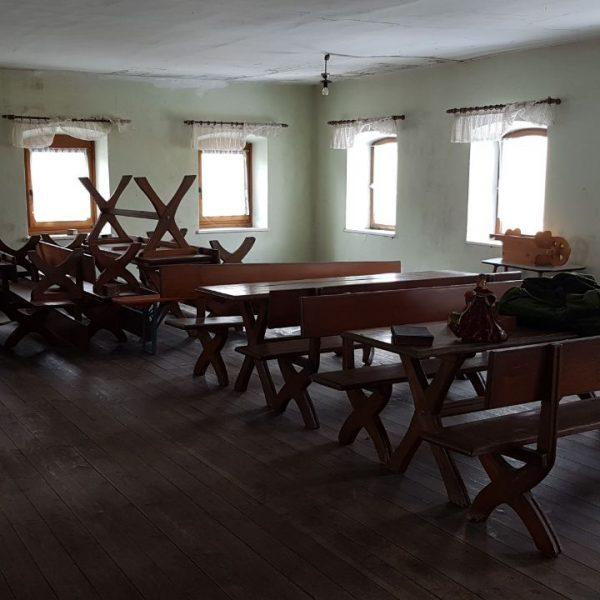 Innenaufnahme von einem Raum mit Bänken und Tischen