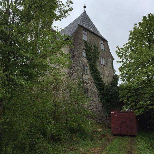 Altes hohe Haus in einem Waldgebiet mit Container zur Entrümpelung davor