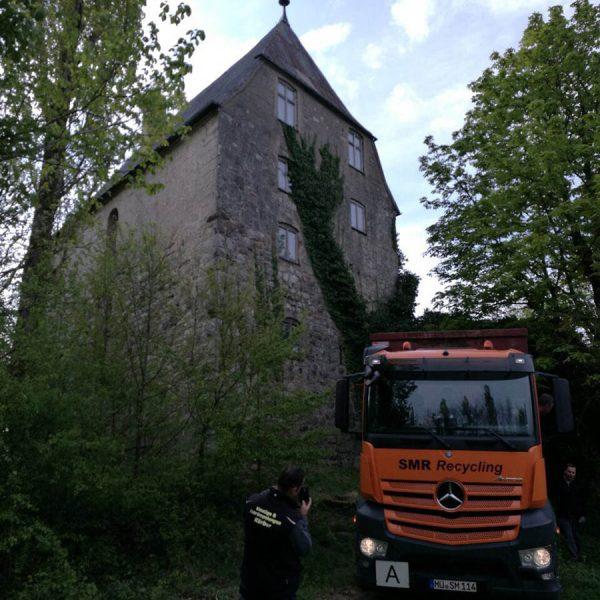 Altes hohes Haus umgeben von Bäumen mit einem orangen LKW und einem Fahrer davor. Auf dem Lastwagen steht Recycling