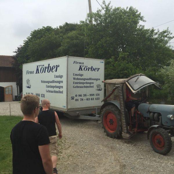 """Traktor mit Anhänger mit Aufschrift """"Firma Körber"""" Umzüge, Wohungsauflösungen, Entrümpelungen, Gebrauchtmöbel"""""""