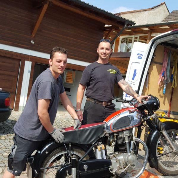 Bild von einem Motorrad, zwei Männer die beim Umziehen helfen