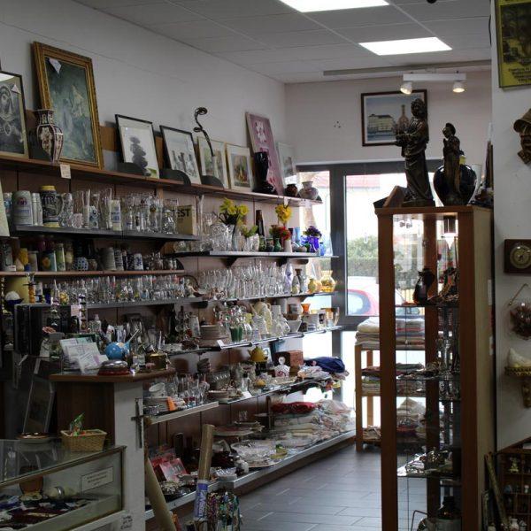 Körber Gebrauchtwarenladen für Möbel und Accessoires - Innenaufnahme mit einer großen Anzahl von gebrauchten Artikeln, wie Schilder, Figuren, Glas, Besteck, Bilder und Uhren
