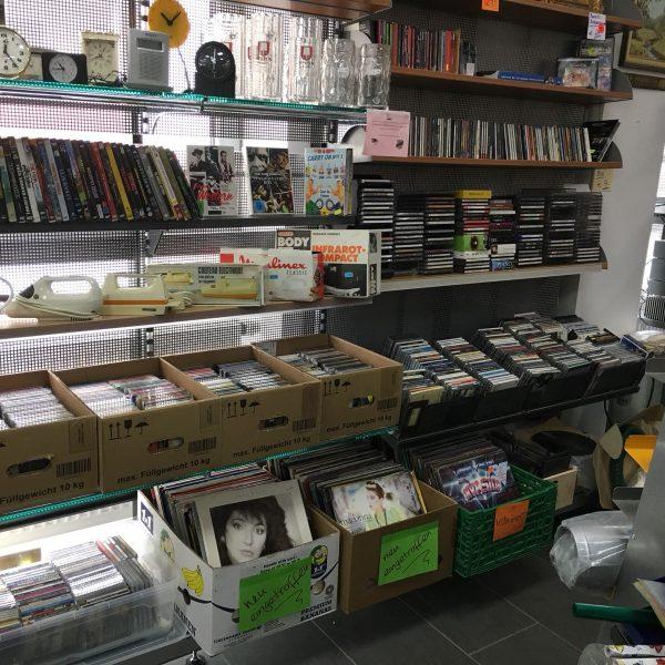 Aufnahme von Gläsern, DVDs, CDs, Uhren und Schallplatten in einem Regal